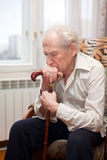 Sad Old Man. Sad lonely old man sitting in an armchair with his cane Stock Images