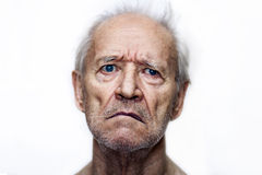 The sad old man with blue eyes stock photography