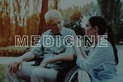 Sad Old Man . Good Medicine in Nursing Home . Sad Old Man. Doctor Calms Old Man. Disabled in Wheelchair. Good Medicine in Nursing Home. Old Man in Sunny Park stock photography