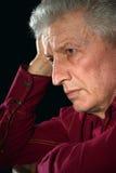 Sad old man. Portrait of a sad old man on a black background close-up stock image