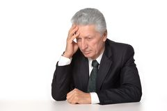 Sad old man sitting. On a background stock photo