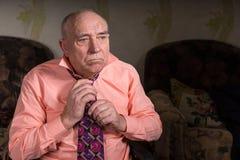 Sad old man tying his tie Stock Image