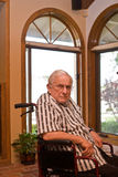 Sad old man in wheelchair. A senior citizen, grandpa, sits in a wheelchair by two big arched windows indoors and has direct eye contact with the camera.  He has Royalty Free Stock Photo