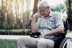 Sad old man in a wheelchair on the park. Sad old man in a wheelchair pensively sitting in summer park stock photo
