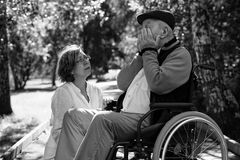 Sad old man on wheelchair and young woman in the park. Sad old men on wheelchair and young female medical assistant in the park in the moment of despair royalty free stock photo