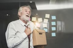 So sad old retired man holding box in office backs to home.  royalty free stock photos