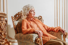 Sad old rich lady is completely alone. Richness is loneliness. Pensive senior woman is sitting on luxury armchair and staring forward with sadness Royalty Free Stock Image