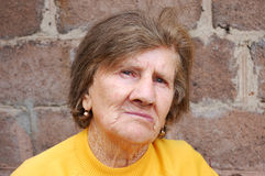 Sad old woman. In the yellow blouse Stock Images