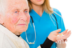 Sad old woman with drugs. Sad old women receiving drugs from the doctor in the background Royalty Free Stock Image