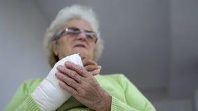 Sad senior woman having pain sitting and holding her injured hand in bandages stock image