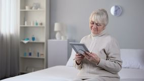 Sad old woman looking at picture of her husband, sitting on bed in living room