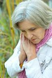 Sad old woman in park Stock Photography