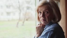 Sad old woman turning her head and looking into the camera. Close-up of sad old woman turning her head and looking into the camera stock footage