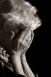 Sad Old Women with her hands to her face is dismay. On black royalty free stock images