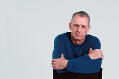 Sad older man. Unhappy older man seated looking down stock images