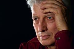 Sad older man on a. Close-up portrait of a sad older man on a black background stock images