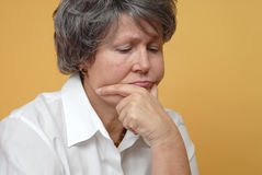 Sad older woman. Very sad older woman in thought on yellow background Royalty Free Stock Image