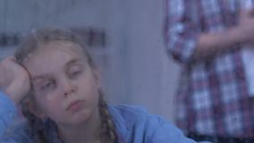 Sad orphan girl looking at rain, couple standing behind, foster family coming. Stock footage stock video footage