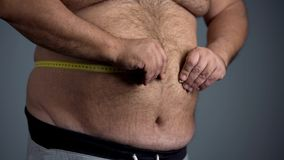 Sad overweight man unable to measure his waist, fat tummy with stretch marks Stock Image