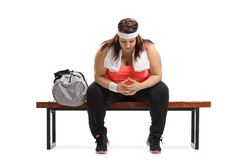 Sad overweight woman sitting on a wooden bench next to a sports. Bag isolated on white background stock photography