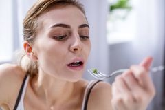 Sad pale woman holding a fork. Small meal. Sad pale woman holding a for while eating a pea royalty free stock images