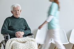 Sad paralyzed elderly man in the wheelchair in the nursing house. Sad paralyzed elderly men in the wheelchair in the nursing house. Motion of doctor stock image