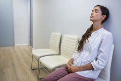 Sad patient with eyes closed sitting on chair at hospital. Sad patient with eyes closed sitting on chair in waiting room at hospital stock photography