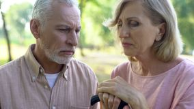Sad pensioner couple sitting bench, retirement poverty, health problem, despair. Stock photo royalty free stock photography