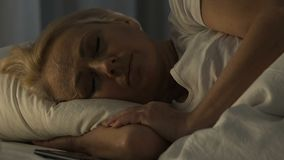 Sad pensioner female chatting on smartphone and trying to sleep, insomnia. Stock footage stock video footage