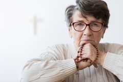 Sad pensioner with rosary royalty free stock photo