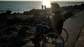 Male wheelchair user is looking on sea and thinking in spring evening