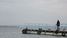 Sad pensive man walks on the pier and walks to the edge stock video footage