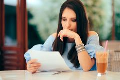 Worried Woman Reading Document Papers in a Restaurant royalty free stock image