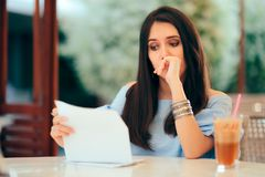 Worried Woman Reading Document Papers in a Restaurant stock photography