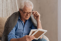 Sad pessimistic man fixing his glasses. Important people. Sad pessimistic senior man fixing his glasses and looking at the photograph while holding them Royalty Free Stock Photo