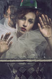 Sad Pierrot woman behind the glass. Sad red Pierrot woman behind the glass Stock Images