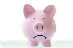 Sad piggy. Frowning pink piggy bank, on white Royalty Free Stock Images