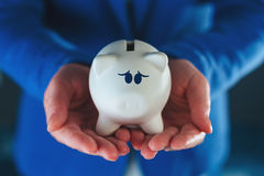 Sad piggy coin bank in businesswoman`s hands Royalty Free Stock Photo