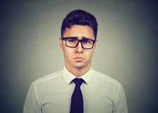 Sad pity looking business man. Sad pity looking young business man in glasses on gray wall background Royalty Free Stock Images