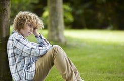 SAD pojke som sitter i Park arkivfoto