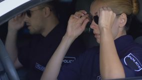 Sad police woman and male partner getting in car, depressed about lost criminal stock video
