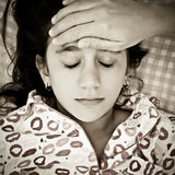 Sad portrait of a small girl sick with fever Royalty Free Stock Photos