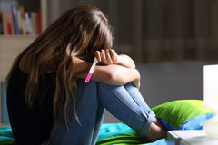 Sad pregnant teen after pregnancy test. Side view of a sad pregnant teen sitting on her bed after checking a pregnancy test with a dark light in the background stock photos