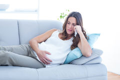 Sad pregnant woman lying on sofa Stock Photo