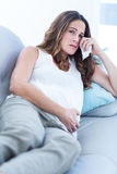 Sad pregnant woman relaxing on sofa Stock Photos