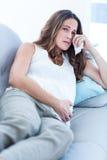 Sad pregnant woman relaxing on sofa Stock Photos