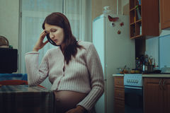 Sad pregnant woman sitting in the kitchen. Royalty Free Stock Photos