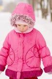 Sad preschool child in pink coat. In park Stock Photo