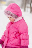 Sad preschool child in pink coat. In park Stock Image