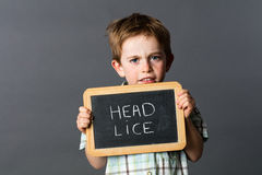 Sad preschool kid protecting from head lice behind school slate Stock Image